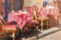 Tablas de café francés al aire libre tradicional en París Imágenes de archivo libres de regalías