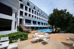 Tablas en la piscina, ociosos del sol al lado del jardín y edificios Fotografía de archivo