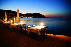 Tablas en una 'promenade' de la playa en la ciudad de Skopelos en la puesta del sol fotografía de archivo