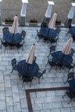 Tablas exteriores del restaurante del comedor del patio con los paraguas Fotos de archivo