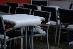 Tablas exteriores del restaurante en primavera con nieve encendido imagen de archivo libre de regalías