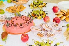 Tablas servidas en el banquete Postres, fruta y pasteles en la comida fría abastecimiento foto de archivo