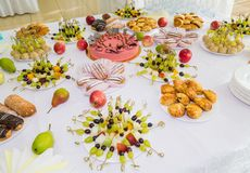 Tablas servidas en el banquete Postres, fruta y pasteles en la comida fría Vidrio abastecimiento imagen de archivo