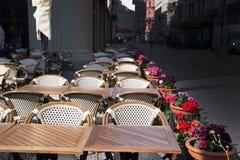 Tablas, sillas y flores en potes en café de la acera Fotografía de archivo