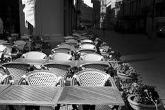 Tablas, sillas y flores en potes en café de la acera Imágenes de archivo libres de regalías