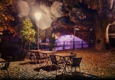 Tablas vacías debajo de una lámpara en la noche en la niebla en la costa de la ciudad Fotos de archivo libres de regalías
