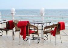 Tablas vacías en el restaurante del hotel con las telas escocesas rojas en la playa Imágenes de archivo libres de regalías