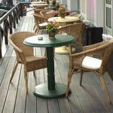 Tablas y butacas en un primer del café de la calle Foto de archivo