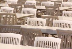 Tablas y sillas blancas en terraza del restaurante Fotos de archivo