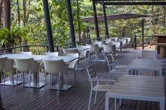 Tablas y sillas blancas en un restaurante en el bosque Foto de archivo
