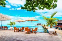 Tablas y sillas con las sombrillas en un embarcadero de madera contra el agua azul del océano y de las casas de planta baja de ma fotografía de archivo