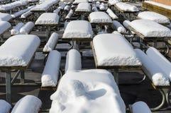 Tablas y sillas cubiertas con nieve Imágenes de archivo libres de regalías