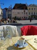Tablas y sillas de los cafés de la calle en la gente que espera de la ciudad vieja para relajar y para tener una taza de restaur foto de archivo libre de regalías
