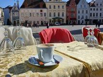 Tablas y sillas de los cafés de la calle en la gente que espera de la ciudad vieja para relajar y para tener una taza de restaur imagen de archivo libre de regalías