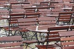 Tablas y sillas de madera mojadas al aire libre debajo de la lluvia Fotos de archivo