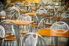 Tablas y sillas en interior de la zona de restaurantes Imágenes de archivo libres de regalías