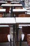 Tablas y sillas en la calle en nieve Imagen de archivo libre de regalías