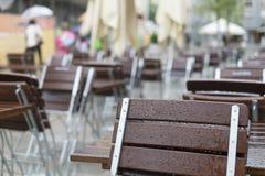 Tablas y sillas vacías delante de un restaurante en la lluvia Imagen de archivo