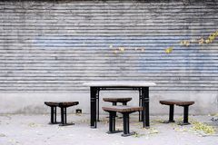 Table,Chairs and wall with Fall ivy. One table,four chairs and wall behind with Fall ivy in a garden royalty free stock image