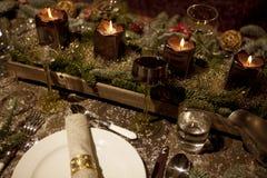 Table étendue par Noël dans la lueur d'une bougie Images stock