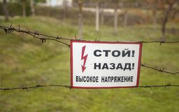 Table with alert Stop Backward High Voltage. On barbed wire Stock Photo