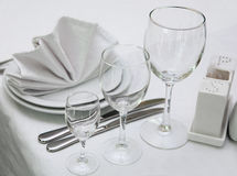 Table appointments. With plates and wine glasses stock image