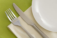 Table appointments. Knife, fork and white plate with beige serviette on a green tablecloth Royalty Free Stock Photography