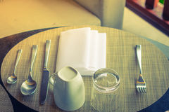 Table appointments- fork,knife,spoon, silk napkin on bamboo mat Royalty Free Stock Image