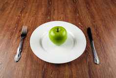 Table appointments and the fresh green apple on a white plate Stock Image
