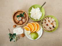 Table Appointments for Healthy Organic Breakfast.Walnuts,Oatmeal and Cottage Cheese.Cut orange and Apple.Green Ceramic and Wooden Royalty Free Stock Photography