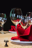 Table appointments and restaurant still life with white plate, fork wine glasses. red napkin. black background, soft Stock Images
