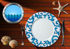 Table Arrangement for Seafood Menu. Empty plate with fork and knife, seashells, starfish and metal porthole with sea waves. Table set for a seafood menu Royalty Free Stock Photography