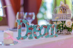 Table arrangements. And decoration details with wooden letters an miniature metal bird cage Stock Image