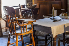 Table and baby chair in very old kitchen Stock Photos