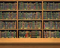 Table on background of bookshelf full of books Stock Photo