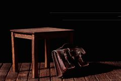 Table and bag. A vintage bag under an old and wooden table royalty free stock images