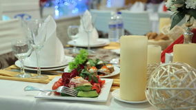 Table in banquet hall is prepared for further celebration. It is full of food, cutlery and special decorative elements. Big wax candles, glass vase with stock footage