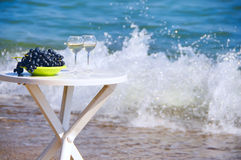 Table on the beach with glasses of wine and grapes. Simple white table on the beach with glasses of wine and grapes. In the background, foam rolling wave and the royalty free stock image