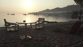 Table on beach waits tourists for breakfast, sunrise early in the morning on the tropical Pemuteran Bali beach, Indonesia. Sunrise early in the morning on the stock video footage