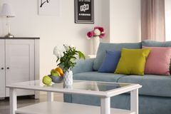 Table with beautiful flowers in elegant interior of living room stock images