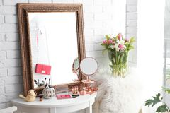 Table with beautiful mirror and cosmetics royalty free stock photos