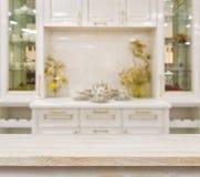 Table beige sur le fond blanc defocused de meubles de cuisine Image stock