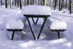 Table and benches in the park after a heavy snowfall. Interesting photo for the site about nature, parks and seasons Royalty Free Stock Photography