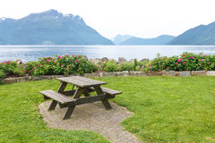 Table and benches for picnic on fjord shore Stock Photos