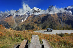 Table and benches for picnic. Snow-capped Alps in beautiful autumn day. Table and benches for picnic on the side of the  road. Great highway winds between Stock Image