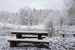 A table with benches on the shore of a lake among the winter sno. W-covered forest Royalty Free Stock Photography