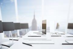 Table blanche dans la salle de conférence avec un ordinateur portable et une grande victoire Image stock