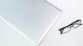 Table blanche de bureau avec les verres et l'ordinateur portable Photographie stock