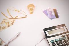 Table blanche de bureau avec les verres et le billet de banque de calculatrice de stylo Photo libre de droits