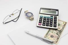 Table blanche de bureau avec les verres et le billet de banque de calculatrice de stylo Image stock